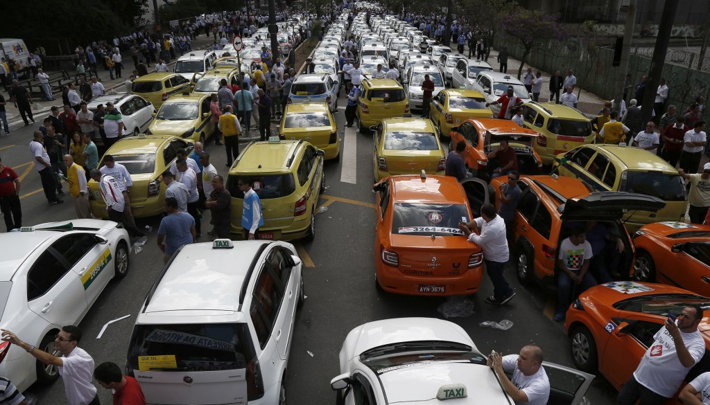 Taxi drivers demonstrate outside the chamber of deputies in the neighborhood of Se, Sao Paulo, Brazil, on September 9, 2015, against the use of the Uber application in the country. The demonstration was called by the Brazilian association of taxi unions. AFP PHOTO / Miguel SCHINCARIOL